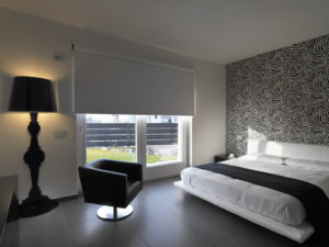 A bedroom with grey tile floors